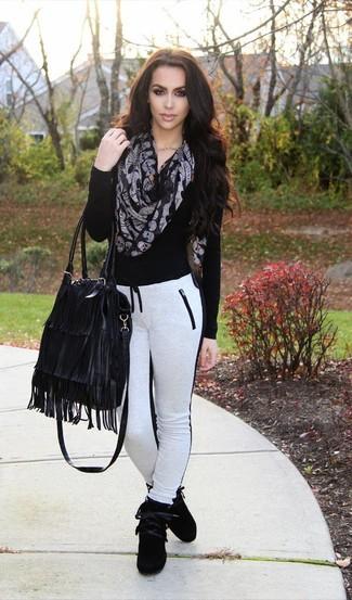 Cómo combinar: bolsa tote de cuero сon flecos negra, zapatillas altas de ante negras, pantalón de chándal en blanco y negro, jersey de pico negro