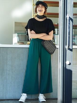 Combinar unos pantalones anchos verde oscuro: Opta por una camiseta con cuello circular con volante negra y unos pantalones anchos verde oscuro para crear una apariencia elegante y glamurosa. ¿Quieres elegir un zapato informal? Opta por un par de zapatillas altas de lona blancas para el día.