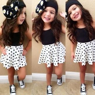 Cómo combinar: zapatillas negras, falda a lunares blanca, camiseta sin manga negra