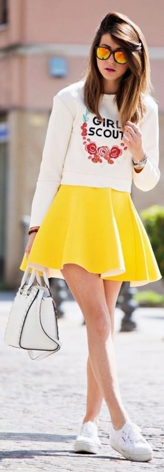Cómo combinar: bolso de hombre de cuero blanco, zapatillas plimsoll blancas, falda skater amarilla, jersey con cuello circular estampado blanco