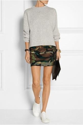 Cómo combinar: cartera sobre de cuero en marrón oscuro, zapatillas plimsoll blancas, minifalda de camuflaje verde oliva, jersey con cuello circular gris