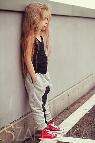 Cómo combinar: zapatillas rojas, pantalones grises, camiseta sin manga negra