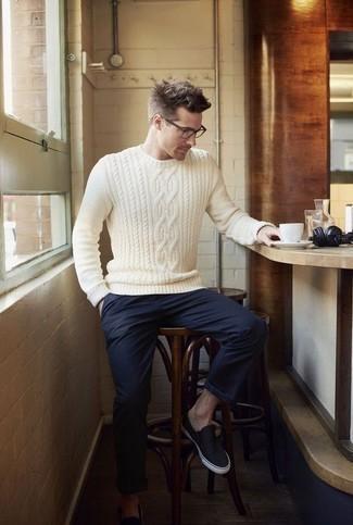 Combinar un jersey de ochos blanco: Para crear una apariencia para un almuerzo con amigos en el fin de semana intenta ponerse un jersey de ochos blanco y un pantalón chino azul marino. Zapatillas slip-on de lona azul marino son una opción buena para completar este atuendo.