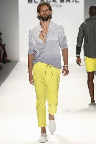 Cómo combinar: pulsera en beige, zapatillas slip-on blancas, pantalón chino amarillo, camisa de manga larga gris