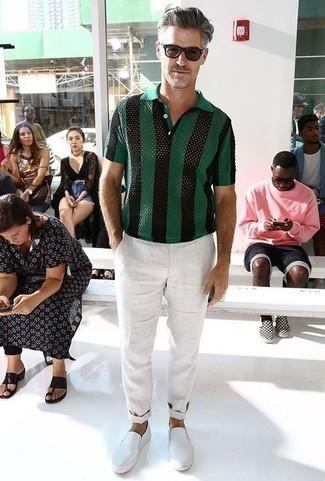Outfits hombres: Equípate una camisa polo de rayas verticales verde oscuro con un pantalón chino blanco para una vestimenta cómoda que queda muy bien junta. Completa el look con zapatillas slip-on blancas.