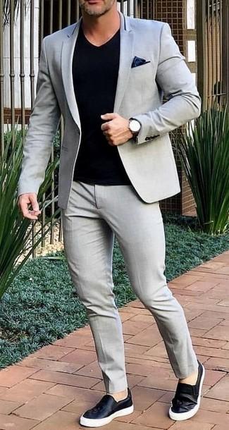 Cómo combinar: pañuelo de bolsillo de seda negro, zapatillas slip-on de cuero negras, camiseta con cuello en v negra, traje gris