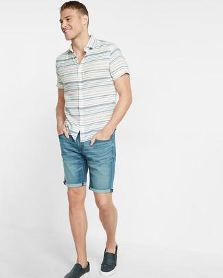 Cómo combinar: zapatillas slip-on de cuero azul marino, pantalones cortos vaqueros azules, camisa de manga corta de rayas horizontales blanca