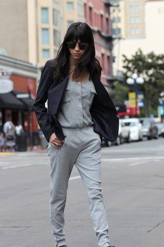 Cómo combinar: zapatillas slip-on de cuero negras, mono gris, blazer de rayas verticales negro