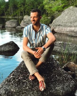 Cómo combinar: reloj plateado, zapatillas slip-on de lona estampadas en multicolor, vaqueros pitillo verde oliva, camisa de manga corta de rayas verticales en blanco y azul