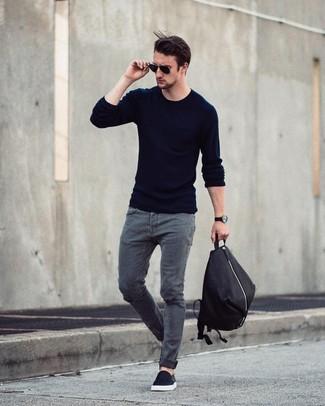 Cómo combinar: mochila negra, zapatillas slip-on negras, vaqueros grises, jersey con cuello circular azul marino