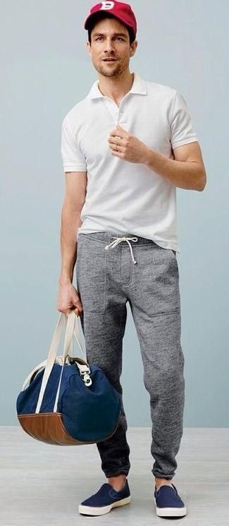 Cómo combinar: bolso baúl de lona azul marino, zapatillas slip-on de lona azul marino, pantalón de chándal gris, camisa polo blanca