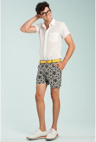 Cómo combinar: correa de lona amarilla, zapatos brogue de ante blancos, pantalones cortos estampados en blanco y negro, camisa de manga corta de rayas verticales blanca