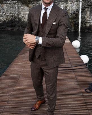Outfits hombres: Empareja un traje de tres piezas en marrón oscuro con una camisa de vestir blanca para rebosar clase y sofisticación. Si no quieres vestir totalmente formal, opta por un par de zapatos brogue de cuero marrónes.