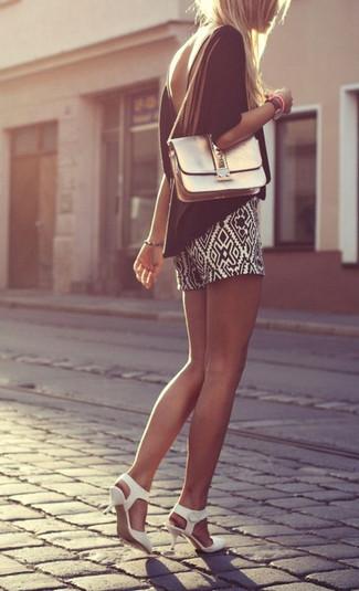 Cómo combinar: bolso bandolera de cuero dorado, zapatos de tacón de cuero blancos, pantalones cortos con estampado geométrico en negro y blanco, blusa de manga corta negra