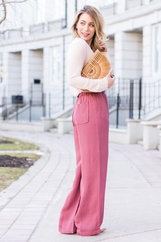 Cómo combinar: cartera sobre de paja marrón claro, zapatos de tacón de cuero en beige, pantalones anchos rosa, blusa de manga larga rosada