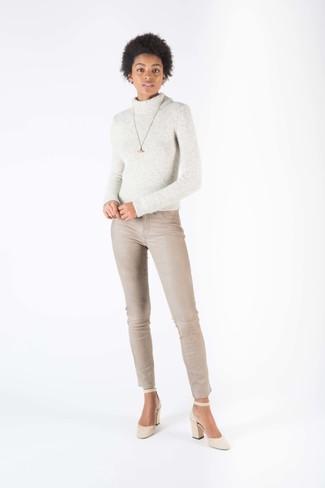 Cómo combinar: colgante dorado, zapatos de tacón de ante en beige, vaqueros pitillo en beige, jersey de cuello alto de lana de punto gris