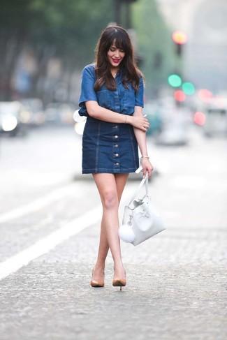 Cómo combinar: mochila con cordón de cuero blanca, zapatos de tacón de cuero marrón claro, falda con botones vaquera azul marino, camisa de manga corta vaquera azul