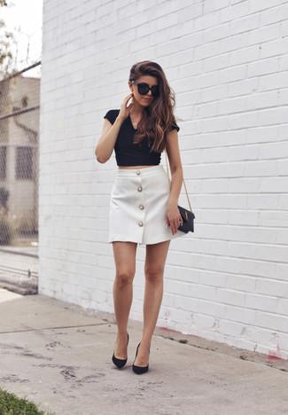 Un top corto de vestir con unos zapatos de tacón negros: Elige un top corto y una falda con botones blanca para conseguir una apariencia relajada pero chic. Zapatos de tacón negros son una opción incomparable para completar este atuendo.