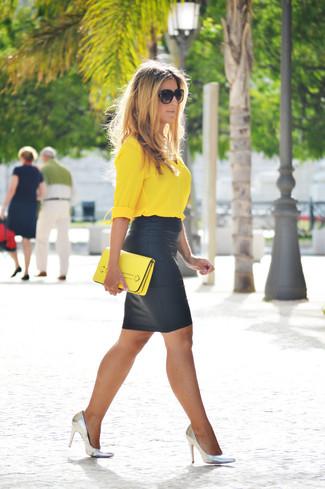 Cómo combinar: cartera sobre de cuero amarilla, zapatos de tacón de cuero plateados, falda lápiz de cuero negra, blusa de botones amarilla