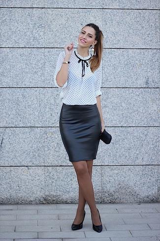 Cómo combinar: cartera sobre de satén negra, zapatos de tacón de cuero negros, falda lápiz de cuero negra, blusa de manga larga a lunares en blanco y negro