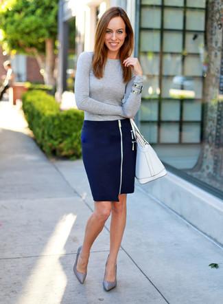 Cómo combinar: bolsa tote de cuero blanca, zapatos de tacón de cuero grises, falda lápiz azul marino, jersey con cuello circular gris