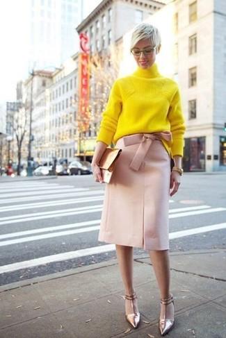 Cómo combinar: cartera sobre de cuero dorada, zapatos de tacón de cuero dorados, falda lápiz rosada, jersey de cuello alto de punto amarillo
