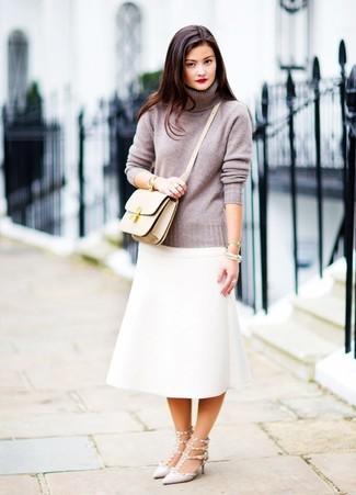 Cómo combinar: bolso bandolera de cuero en beige, zapatos de tacón de cuero con tachuelas grises, falda midi blanca, jersey de cuello alto gris