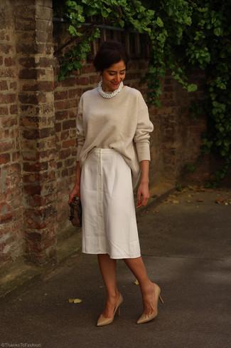 Cómo combinar: cartera sobre de cuero marrón, zapatos de tacón de cuero marrón claro, falda midi blanca, jersey oversized en beige