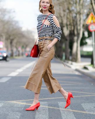 Cómo combinar: bolso bandolera de cuero rojo, zapatos de tacón de cuero rojos, falda pantalón de cuero marrón claro, camiseta de manga larga de rayas horizontales en blanco y negro