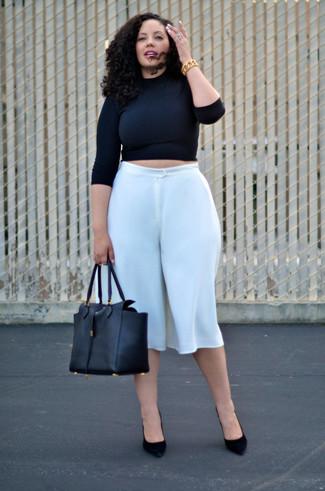 Cómo combinar: bolsa tote de cuero negra, zapatos de tacón de ante negros, falda pantalón blanca, jersey corto negro