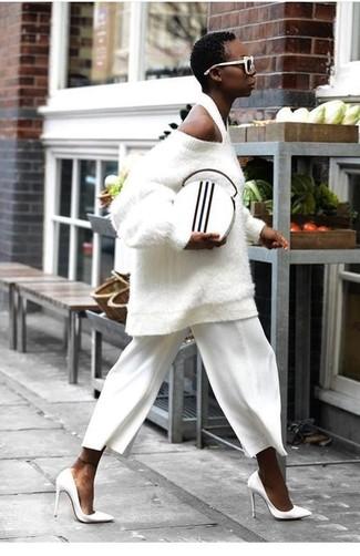 Cómo combinar: cartera sobre de cuero en blanco y negro, zapatos de tacón de cuero blancos, falda pantalón blanca, jersey oversized con relieve blanco