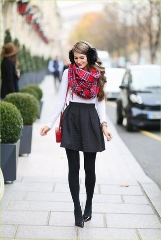 Cómo combinar: bolso bandolera de cuero rojo, zapatos de tacón de cuero negros, falda skater a lunares negra, camiseta de manga larga blanca