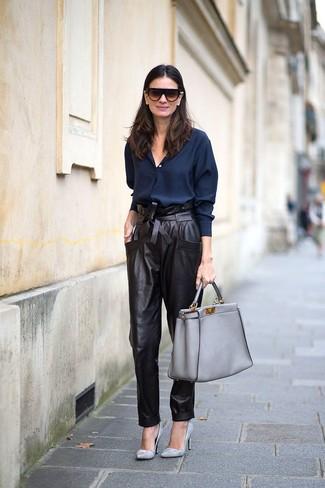 Cómo combinar: bolsa tote de cuero gris, zapatos de tacón de cuero grises, pantalón de pinzas de cuero negro, camisa de vestir azul marino