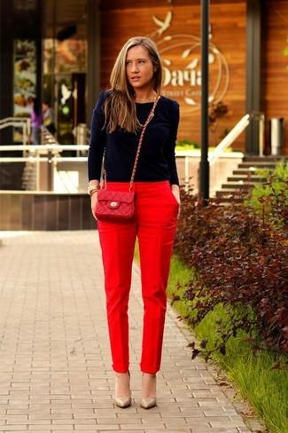 Cómo combinar: bolso bandolera de cuero acolchado rojo, zapatos de tacón de cuero marrón claro, pantalón de pinzas rojo, jersey con cuello circular azul marino