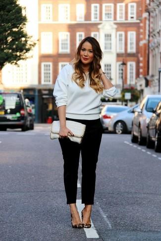 Cómo combinar: cartera sobre de cuero blanca, zapatos de tacón de ante de leopardo marrónes, pantalones pitillo negros, sudadera blanca