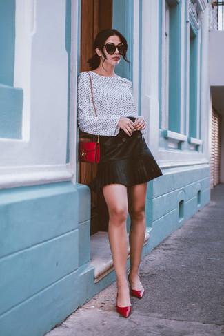 Cómo combinar: bolso bandolera de cuero rojo, zapatos de tacón de cuero rojos, minifalda de cuero plisada negra, blusa de manga larga a lunares en blanco y negro