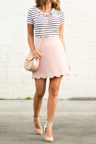 Cómo combinar: bolso bandolera de cuero rosado, zapatos de tacón de ante en beige, minifalda rosada, camiseta con cuello circular de rayas horizontales en blanco y negro