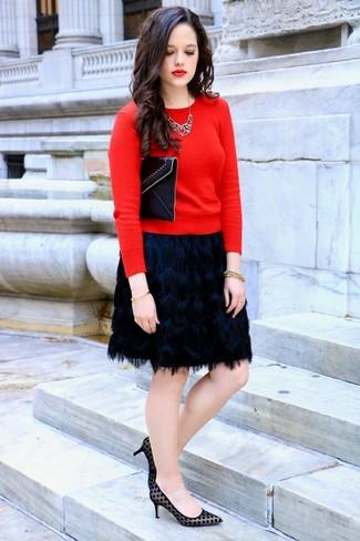 Cómo combinar: cartera sobre de cuero negra, zapatos de tacón de ante a lunares negros, minifalda сon flecos negra, jersey con cuello circular rojo