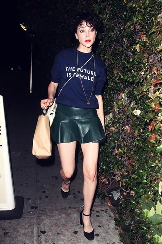 Cómo combinar: bolso bandolera de cuero blanco, zapatos de tacón de ante negros, falda skater de cuero negra, camiseta con cuello circular estampada azul marino