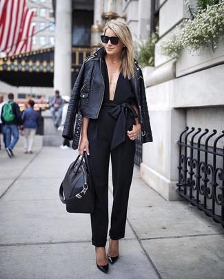 Cómo combinar: bolsa tote de cuero negra, zapatos de tacón de cuero negros, mono negro, chaqueta motera de cuero negra