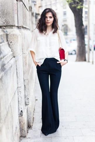 Cómo combinar: bolso de hombre de cuero rojo, zapatos de tacón de cuero negros, pantalón de campana azul marino, camisa de vestir de seda blanca