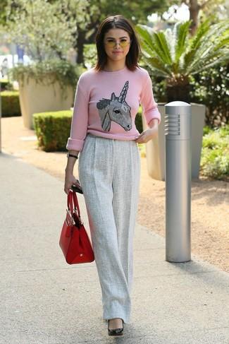 Cómo combinar: bolsa tote de cuero roja, zapatos de tacón de cuero negros, pantalones anchos de lana grises, jersey con cuello circular estampado rosado