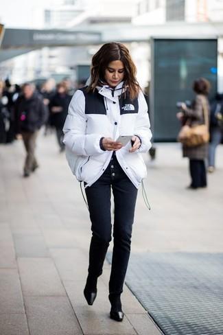 Cómo combinar: calcetines negros, zapatos de tacón de cuero negros, pantalones pitillo negros, plumífero blanco