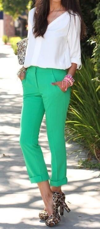 Cómo combinar: cartera sobre de lentejuelas dorada, zapatos de tacón de ante de leopardo marrón claro, pantalón chino verde, blusa de manga larga blanca