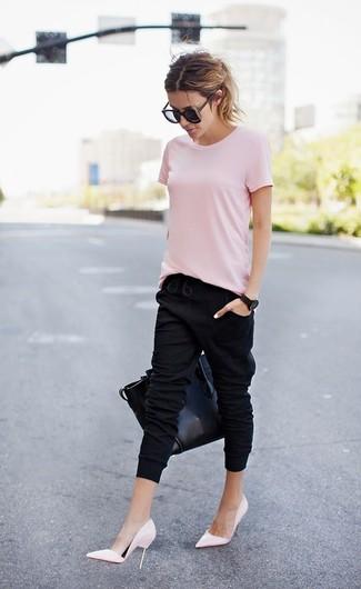 Cómo combinar: bolsa tote de cuero negra, zapatos de tacón de cuero rosados, pantalón de chándal negro, camiseta con cuello circular rosada
