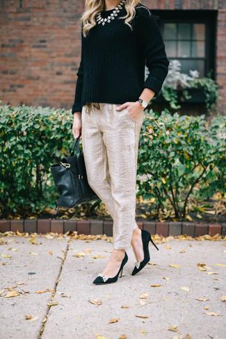 Cómo combinar: bolso de hombre de cuero negro, zapatos de tacón de ante con adornos negros, pantalón de pinzas de seda en beige, jersey con cuello circular negro