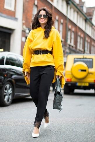 Cómo combinar: bolso de hombre de cuero plateado, zapatos de tacón de cuero blancos, pantalón de pinzas negro, sudadera con capucha amarilla