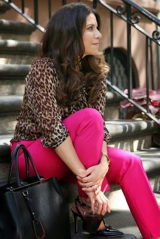 Cómo combinar: bolsa tote de cuero negra, zapatos de tacón de cuero negros, pantalón de vestir rosa, blusa de manga larga de leopardo marrón