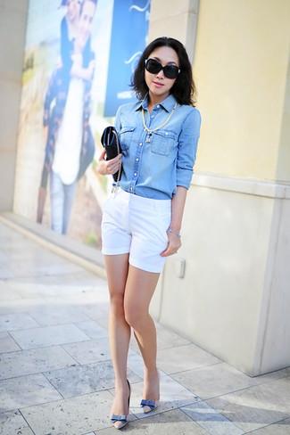 Cómo combinar: cartera sobre de cuero negra, zapatos de tacón de cuero en beige, pantalones cortos blancos, camisa vaquera celeste