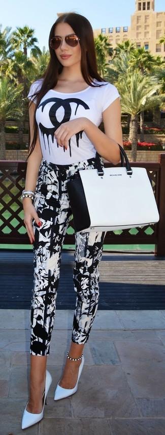 Cómo combinar: bolsa tote de cuero en blanco y negro, zapatos de tacón de cuero blancos, pantalones pitillo estampados en blanco y negro, camiseta con cuello circular estampada en blanco y negro
